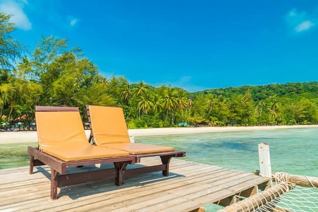 椅子とベッド、木製の桟橋または熱帯のビーチと海とパラダイス島の橋