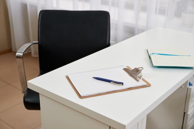 オフィスのテーブルの上の椅子と空白のクリップボードとペン