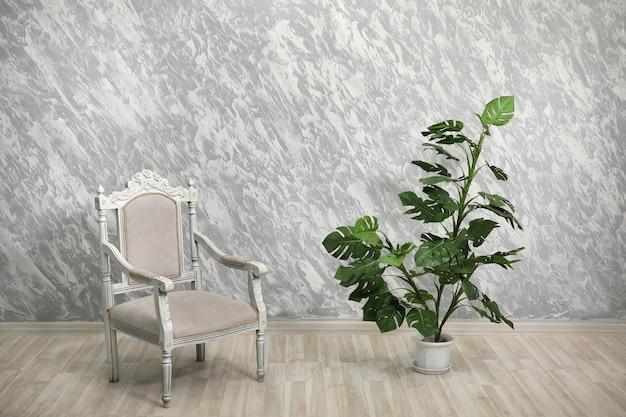 空の明るく塗られた壁の背景にある椅子と屋内植物。