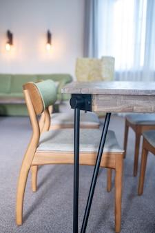 椅子とテーブル。木製の新しい興味深いデザインのテーブルとリビングルームのカーペットの椅子
