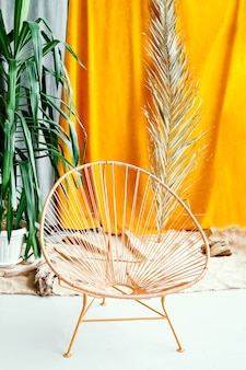 Chair on the background of a palm branch. interior in balinese style. wooden wicker chair