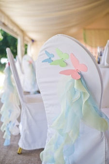 Chair decorated with butterflies made of paper.