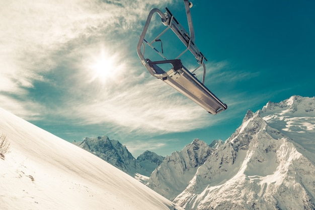 Chair lift on a mountainside on blue sky, snow-capped mountains and a bright winter sun.