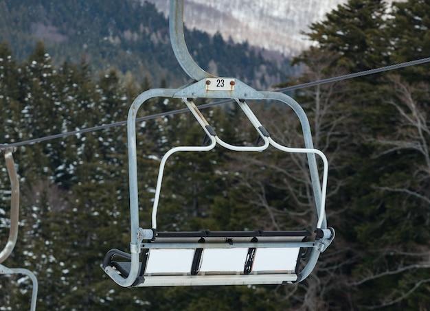 Abetone, 이탈리아에서 눈 덮인 숲 위에 의자 리프트.