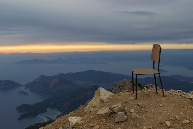 Кресло на вершине горы с закатом на море с льющимися яркими солнечными лучами сквозь облака
