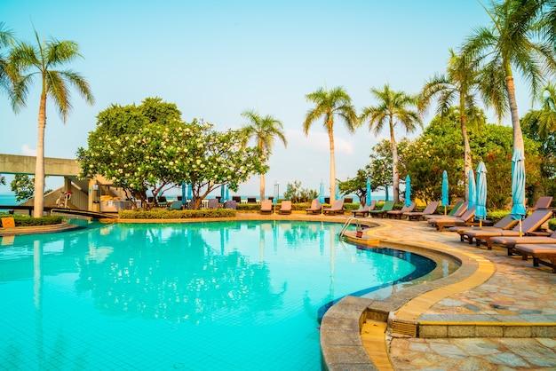 코코넛 야자수와 수영장 주변의 의자 수영장과 우산. 휴일 및 휴가 개념