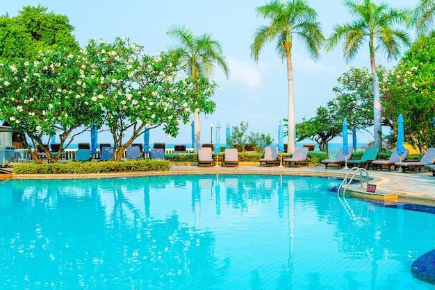 코코넛 야자수가 있는 수영장 주변의 의자 풀과 우산 - 휴일 및 휴가 개념