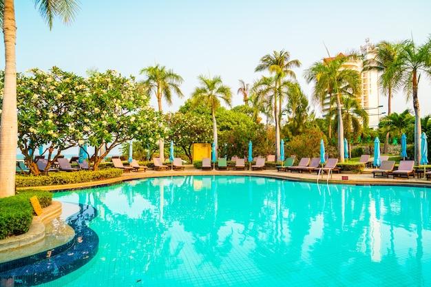 Стул для бассейна и зонт вокруг бассейна с кокосовой пальмой
