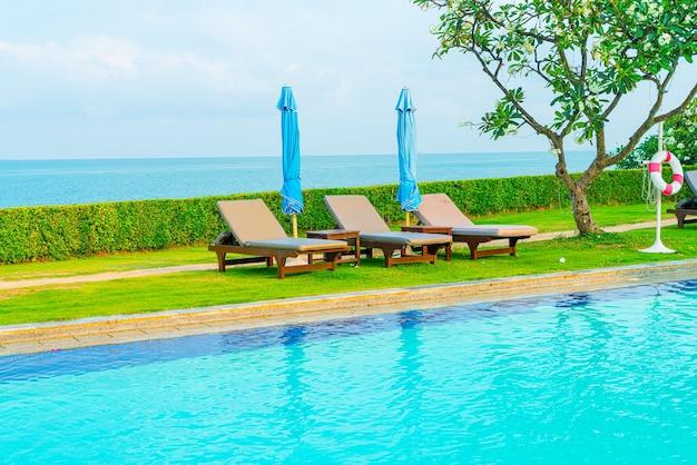 바다 배경이 있는 수영장 주변의 의자 수영장과 우산