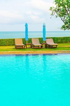 바다 배경이 있는 수영장 주변의 의자 풀과 우산