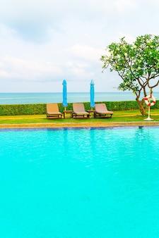 海の海の背景とスイミングプールの周りの椅子プールと傘