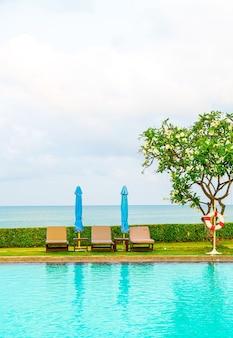 椅子のプールと海の海面を持つプールの周りの傘