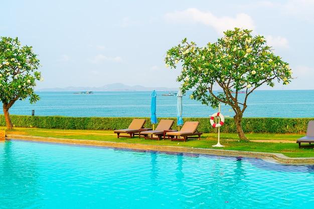 椅子のプールと海の海とスイミングプールの周りの傘