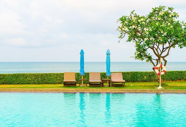 海のあるプールの周りの椅子のプールと傘