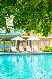 Chair pool around swimming pool in hotel resort - holidays and vacations concept