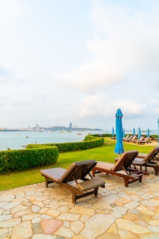 Chair pool or bed pool and umbrella around swimming pool with sea beach at pattaya in thailand