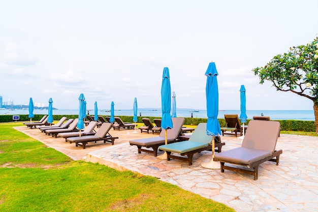 Chair pool or bed pool and umbrella around swimming pool with sea beach surface at pattaya in thailand