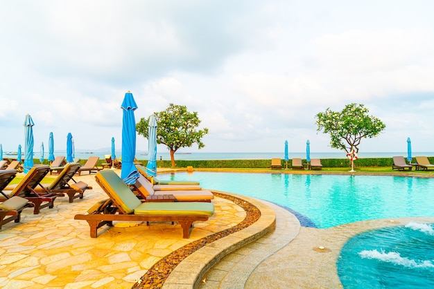 Chair pool or bed pool and umbrella around swimming pool with sea beach views at pattaya in thailand