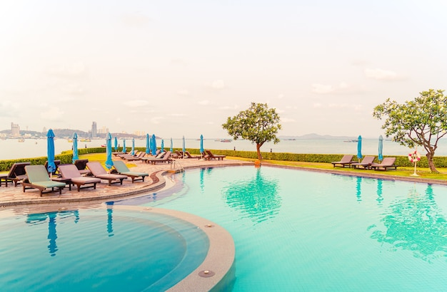 Chair pool or bed pool and umbrella around swimming pool with sea beach views
