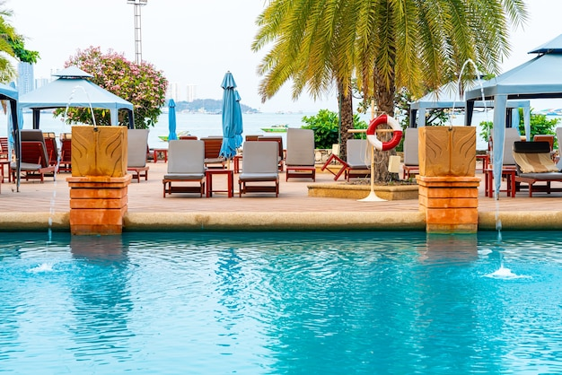Chair pool or bed pool with umbrella around swimming pool