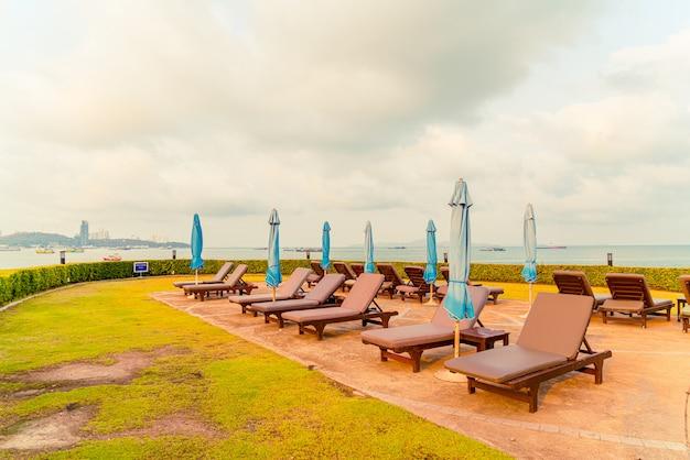 Стул с бассейном или кровать с бассейном и зонтик вокруг бассейна с морским пляжем в паттайе в таиланде