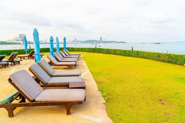 Бассейн со стульями или бассейн с кроватью и зонтик вокруг бассейна с морским пляжем в паттайе в таиланде