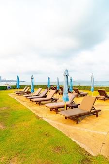 태국 파타야의 바다 해변이있는 수영장 주변의 의자 수영장 또는 침대 수영장과 우산