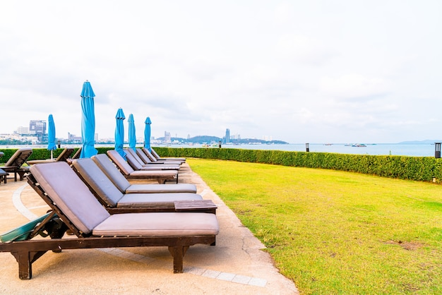 태국 파타야의 바다 해변을 배경으로 하는 수영장 주변의 의자 수영장 또는 침대 수영장 및 우산