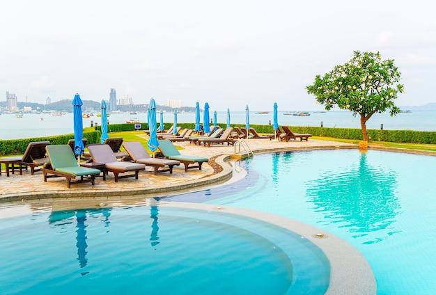 Стул бассейн или кровать бассейн и зонтик вокруг бассейна на фоне морского пляжа