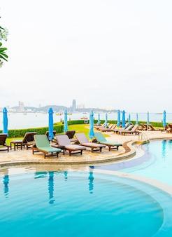 바다 해변을 배경으로 하는 수영장 주변의 의자 수영장 또는 침대 수영장과 우산