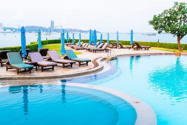 椅子のプールまたはベッドのプールと海のビーチのあるスイミングプールの周りの傘