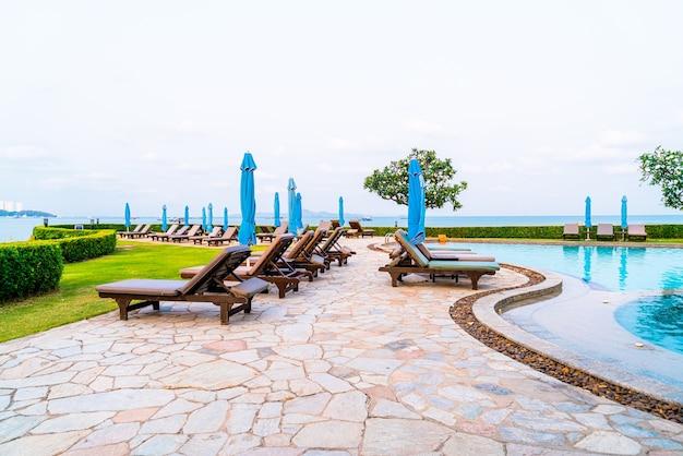 Бассейн со стульями или бассейн с кроватью и зонтик вокруг бассейна с морским пляжем