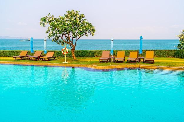 椅子のプールまたはベッドのプールと海のあるプールの周りの傘。休日と休暇の概念