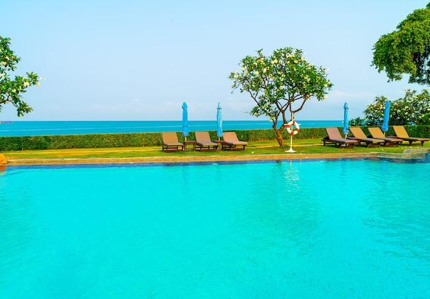 海のあるプールの周りの椅子プールまたはベッドプールと傘