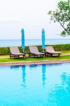 Бассейн со стульями или бассейн с кроватью с зонтиком вокруг бассейна
