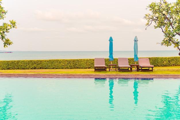 수영장 주변에 우산이있는 의자 수영장 또는 침대 수영장