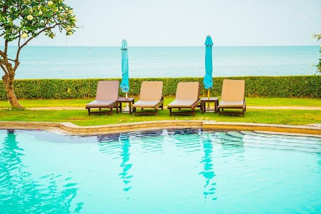 椅子のプールまたはプールの周りの傘が付いているベッドのプール