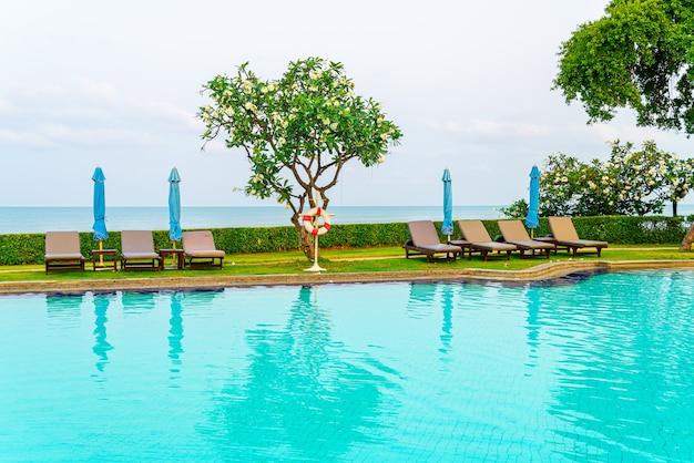 プールの周りに傘が付いている椅子のプールまたはベッドのプール