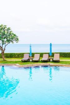 수영장 주변에 우산이 있는 의자 수영장 또는 침대 수영장
