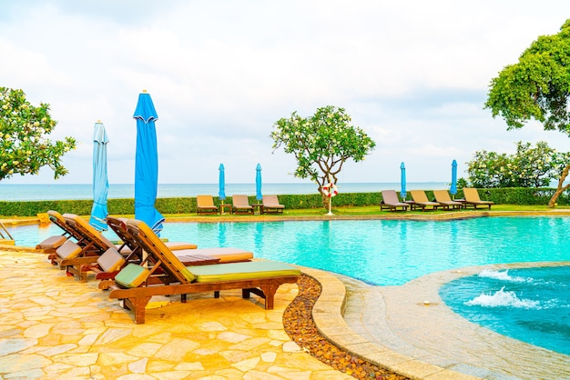 Chair pool and umbrella around swimming pool with ocean sea views