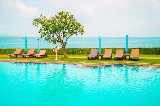 Chair pool and umbrella around swimming pool with ocean sea