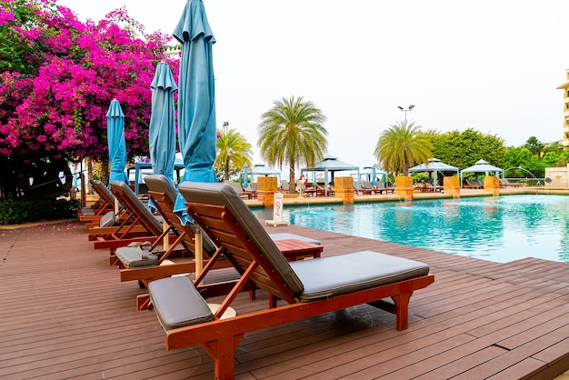 Chair pool with umbrella around swimming pool