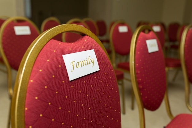 A chair in red velvet with gold and a nameplate family