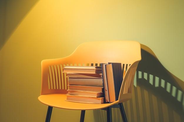 Стул с книгами возле цветной стены