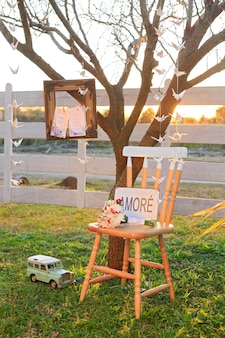 Chair with love sign and vintage photo frame at sunset