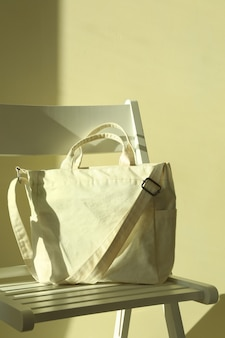 Chair with stylish eco bag against light wall background