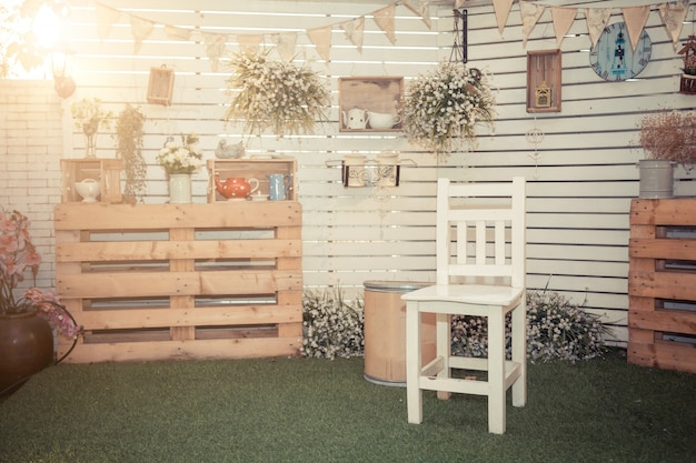 Chair with vintage wooden wall with vintage accessories foreground.
