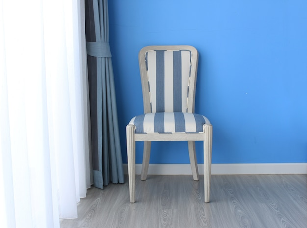 Chair on wooden floor with curtain as background