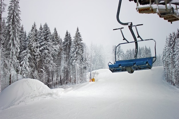 Chairlift in snowy forest on ski slope