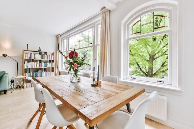 モダンなアパートメントの太陽に照らされたダイニングルームの窓と本棚の近くにある花とキャンドルの椅子と材木テーブル
